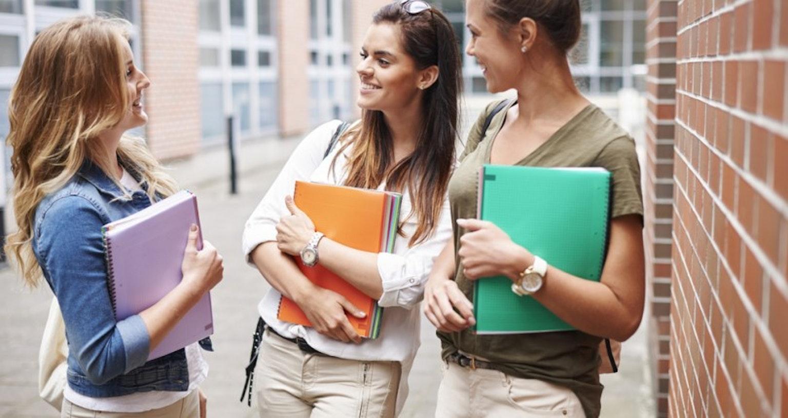 students smiling holding notebooks