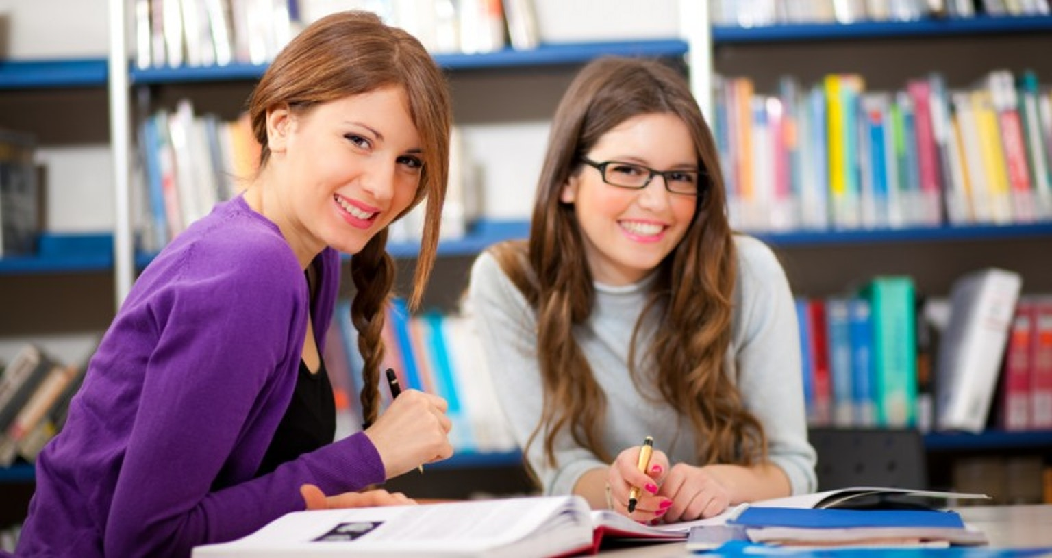 students smiling studying in library