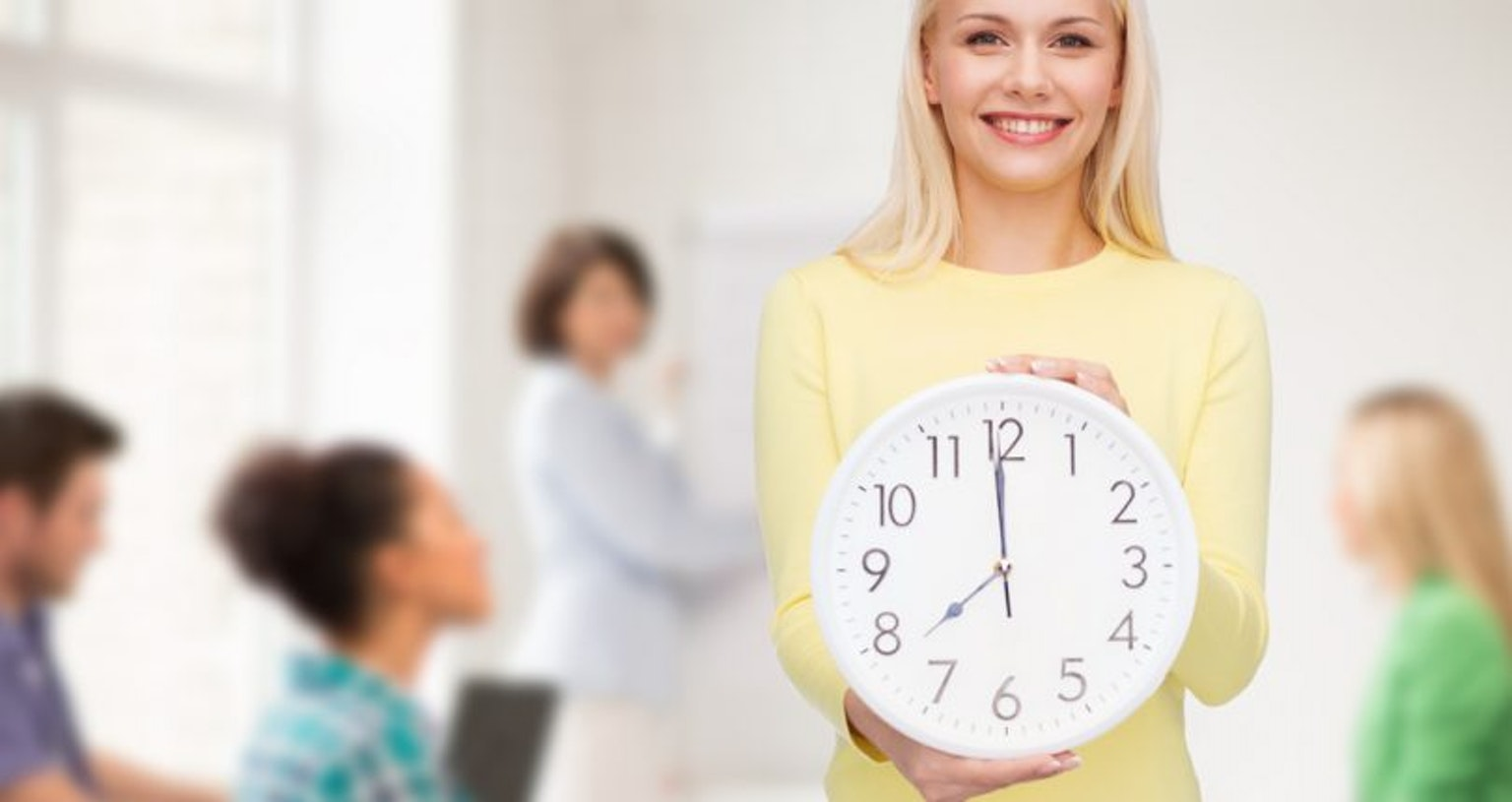 student smiling holding clock